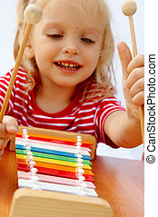 Rainbow xylophone - Little girl wearing striped red t-shirt ...