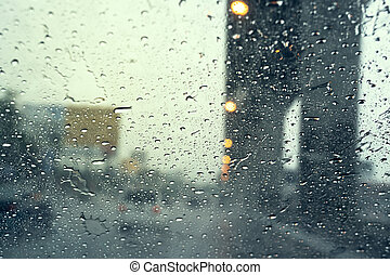 raindrop on the windshield, driving on  road in the city in a rainy day, car windshield view