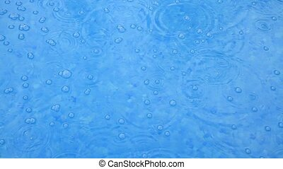 Raindrops are broken with splashes falling on the surface of...
