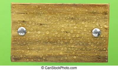 Raindrops fall on a wooden frame, isolated on green. View...