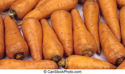 Raindrops falling on rotating carrots. Close-up. Food...