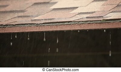 Raindrops falling on the roof of the pavilion in the park, raindrops flow down, close-up