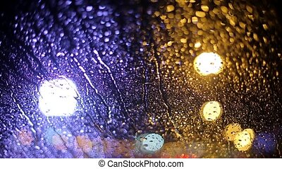 raindrops on a car windshield in the evening lights of the city