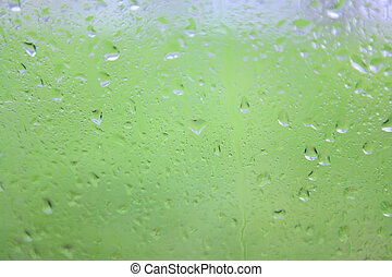 Raindrops on glass of window on green background