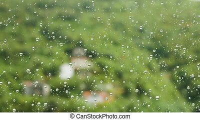 raindrops on glass window at the backdrop of green mountains