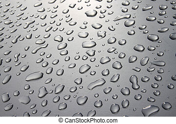 Raindrops on a silver surface with sun shining adding a light effect