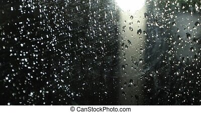 raindrops on the glass at night in front of the lamppost
