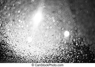 Raindrops on the glass at night. The lanterns are shining. Black and white bokeh. Car glass. Defocus.