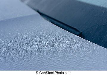 Raindrops on the hood of the car. Close-up.