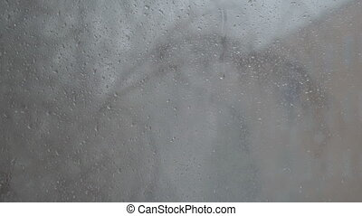 Raindrops on the window glass. Outside the window falling...