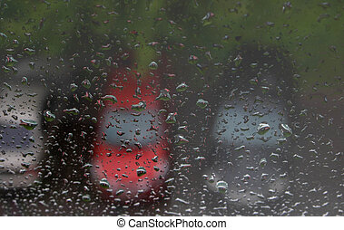 Raindrops on the window, with cars in the Parking lot in the background