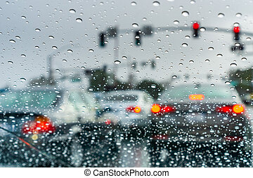 Raindrops on the windshield on a rainy day; cars stopped at a traffic light in the background; California