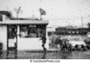 Raindrops on the windshield; Person walking outside during rainy weather in the background; California; black and white