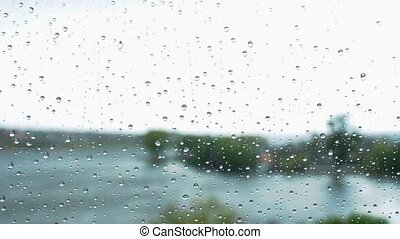 raindrops run down the window glass. Autumn curtains with heavy rain. Gray cold weather outside the window.
