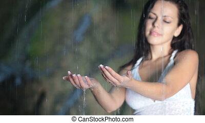 Raindrops splashing on female hand