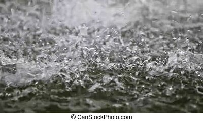 Raindrops splashing over water surface in slow motion 120fps
