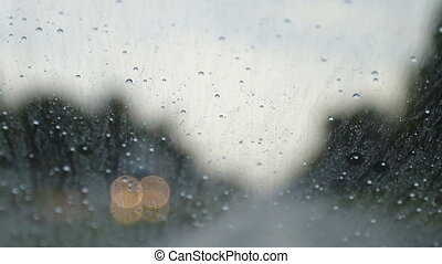 Raindrops trickle down the windshield of moving car on the ...
