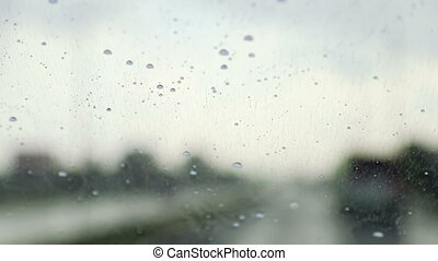 Raindrops trickle down the windshield of moving car. Slow ...