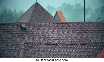 Rainfall over sloped tiled roofs. Slow motion shot -...