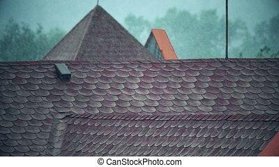Rainfall over sloped tiled roofs. Slow motion shot -...