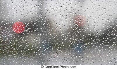 Raininess. Raindrops on window glass and car traffic