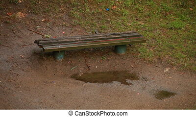 Raining in park with wooden bench