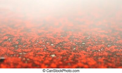 Raining on racetrack in campus stadium. Water on ground. Red...