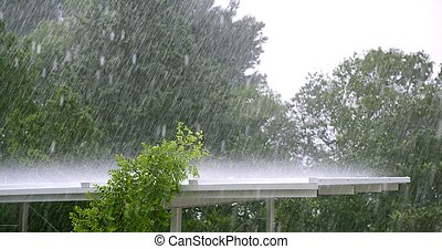 Raining over a white roof in a hurricane storm, trees in...