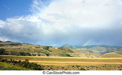 Raining Somewhere - Rainbow appears over distant mountains...