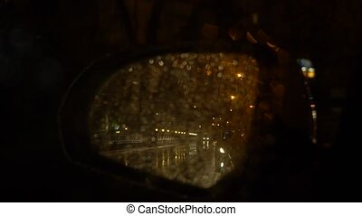 rainwater flow on the rearview mirror. The car stops next to...