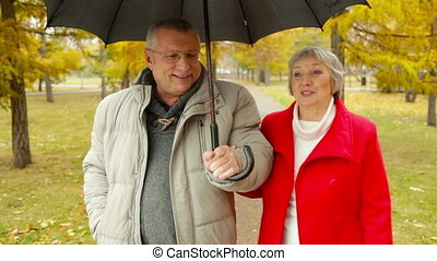 Rainy Autumn - Elderly dates enjoying the walk in the park...