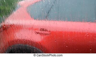 Rainy car window. Red car.