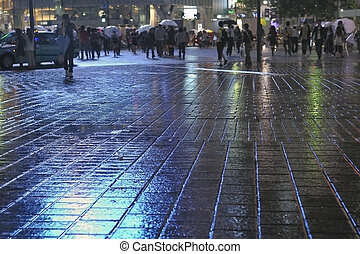 rainy city - rainy pavement reflection by night with crowd...
