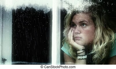 Young girl looking out of a window a rainy day, looking sad.