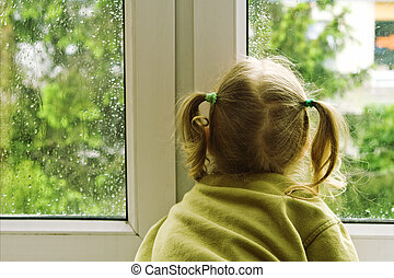 Rainy day - Little girl sitting near the window in the rainy...