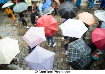 Rainy day - Out of focus shot of people with umbrellas on a...