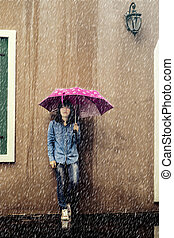 rainy day - rainy season, Woman in jeans and holding a pink...