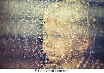 Rainy day - Little boy behind the window in the rain -...