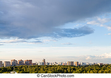 rainy gray cloud in blue evening sky over city