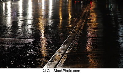 Rainy gutter and street. - Rainy night. Lights from traffic...