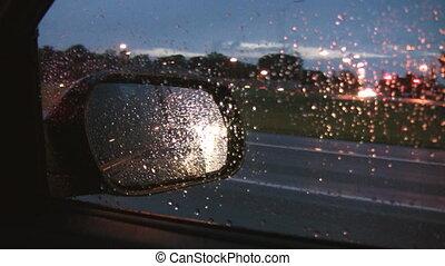 Rainy highway mirror.