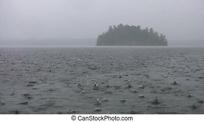 Rainy lake and island. - Heavy rain on lake with island in ...
