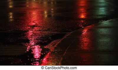 Rainy night. Traffic lights changin