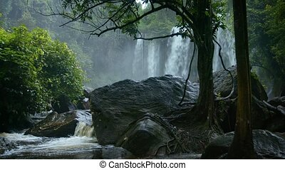 Rainy season in the tropics. Waterfall and a river among...