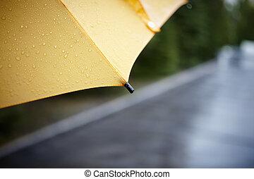 rainy walk with yellow umbrella, selective focus on nearest...