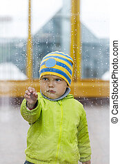 rainy weather and the little boy behind the glass, drops of rain on the window