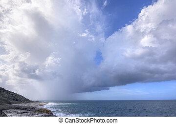 Rainy weather over tropical sea - Rain falls from dark ...