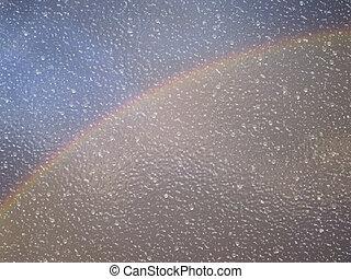 Rainy window with rainbow