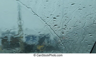 Rainy windshield with cars passing.