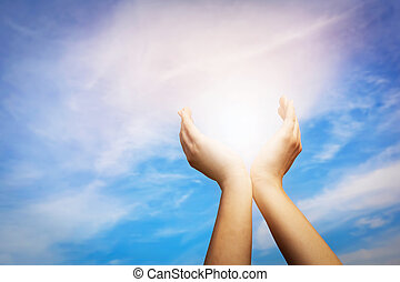 Raised hands catching sun on blue sky. Concept of spirituality, wellbeing, positive energy